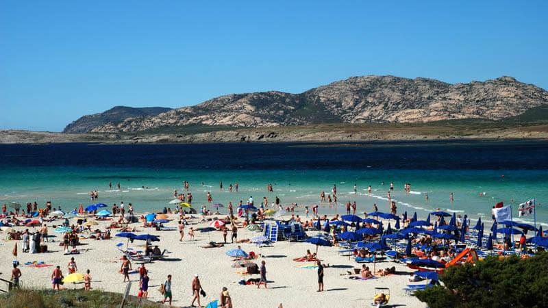Pessoas na praia em Sardenha, na Itália