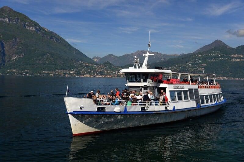 Pessoas em barco passeando pelo Lago Como