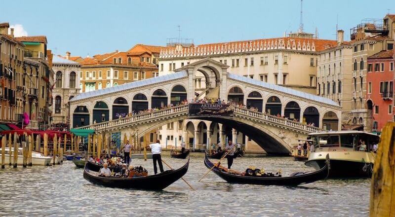 Pessoas fazendo passeio de gôndola em Veneza