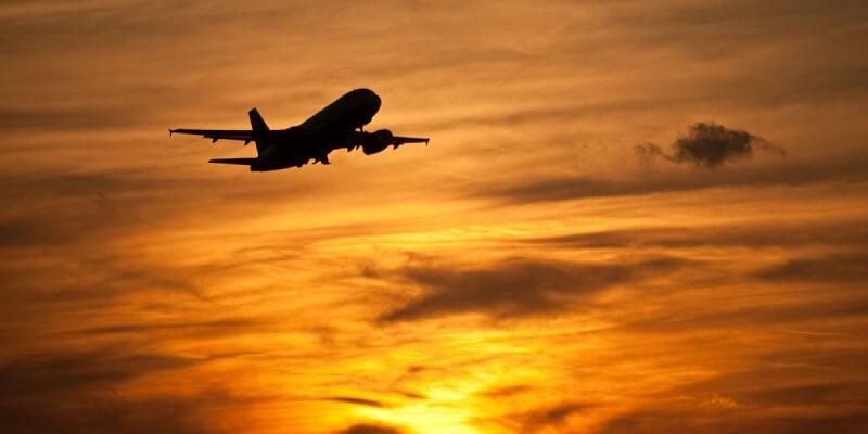 Avião em céu com Sol se pondo
