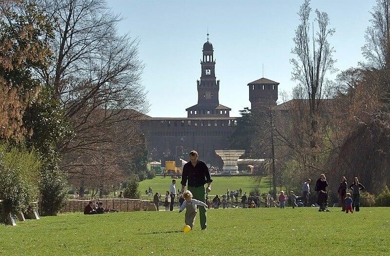 Criança e adulto brincando de bola no Parque Sempione