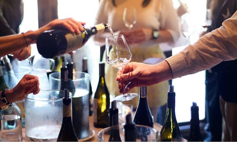 Pessoa servindo vinho em taça