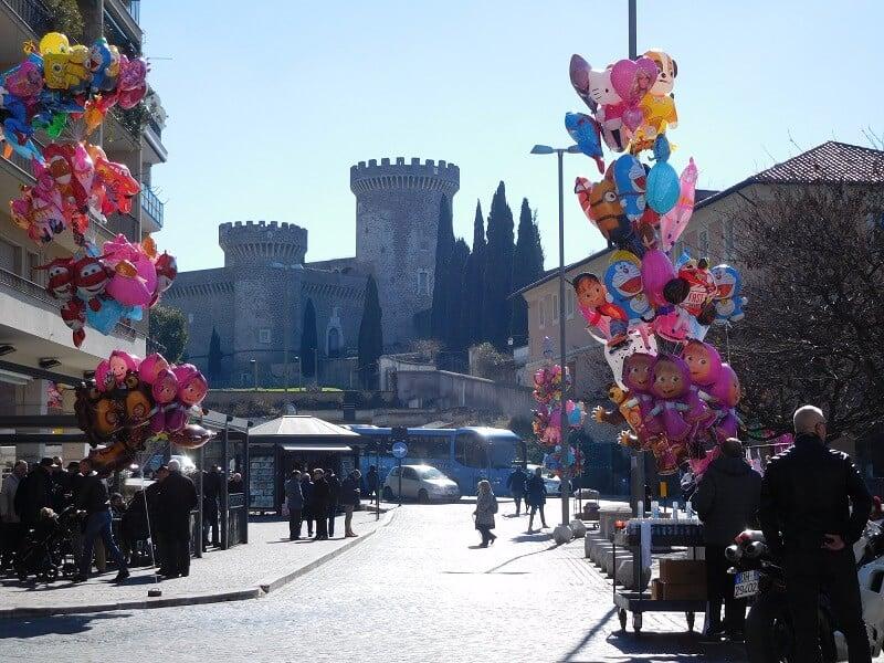 Pessoas agasalhadas e Rocca di Tivoli ao fundo